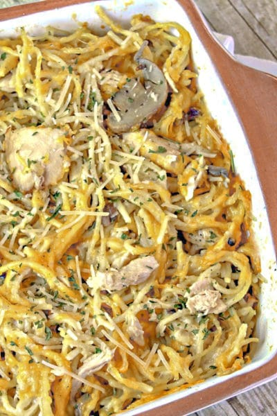 Fully cooked chicken tetrazzini in a casserole dish on wooden background.