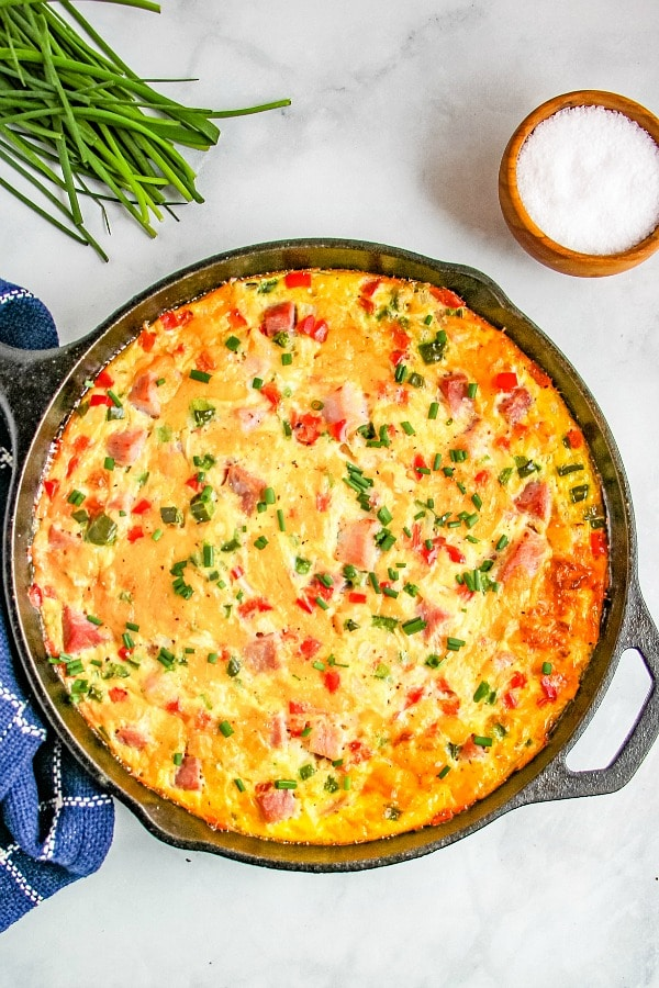 Western Omelette Frittata baked in a cast iron skillet garnished with chives