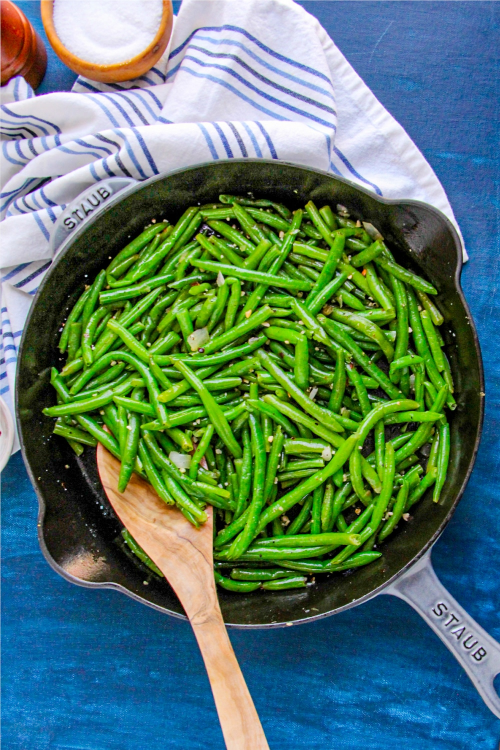 Easy Skillet Green Beans in a skillet with wooden spoon on blue background