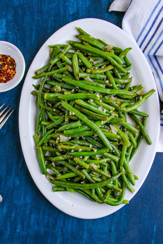Skillet Green Beans on a white platter on blue background