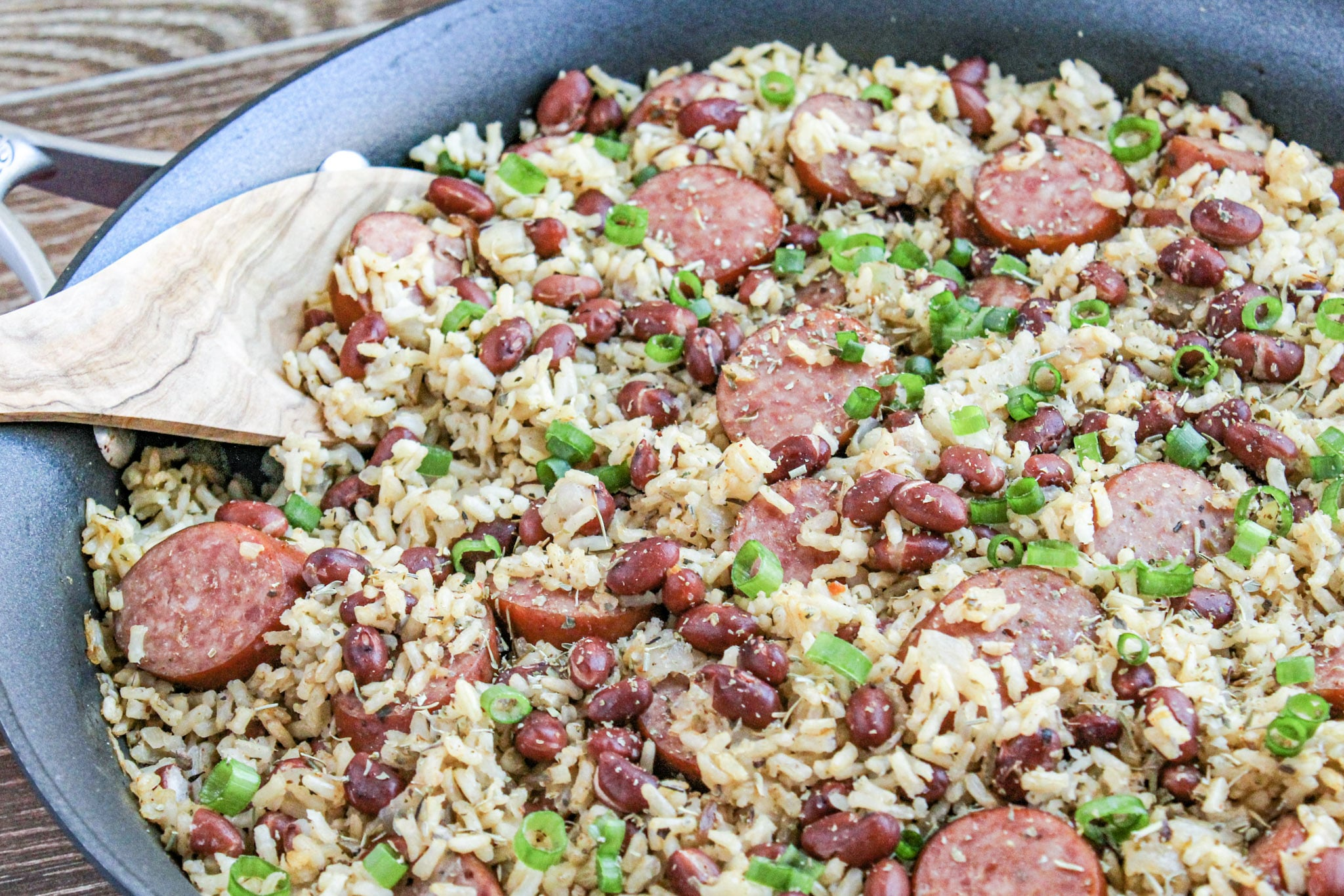 close up photo of red beans and rice in a skillet with wooden spoon and wooden background