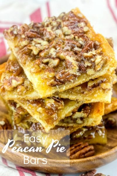 A stack of Pecan Pie Bars on a wood plate.