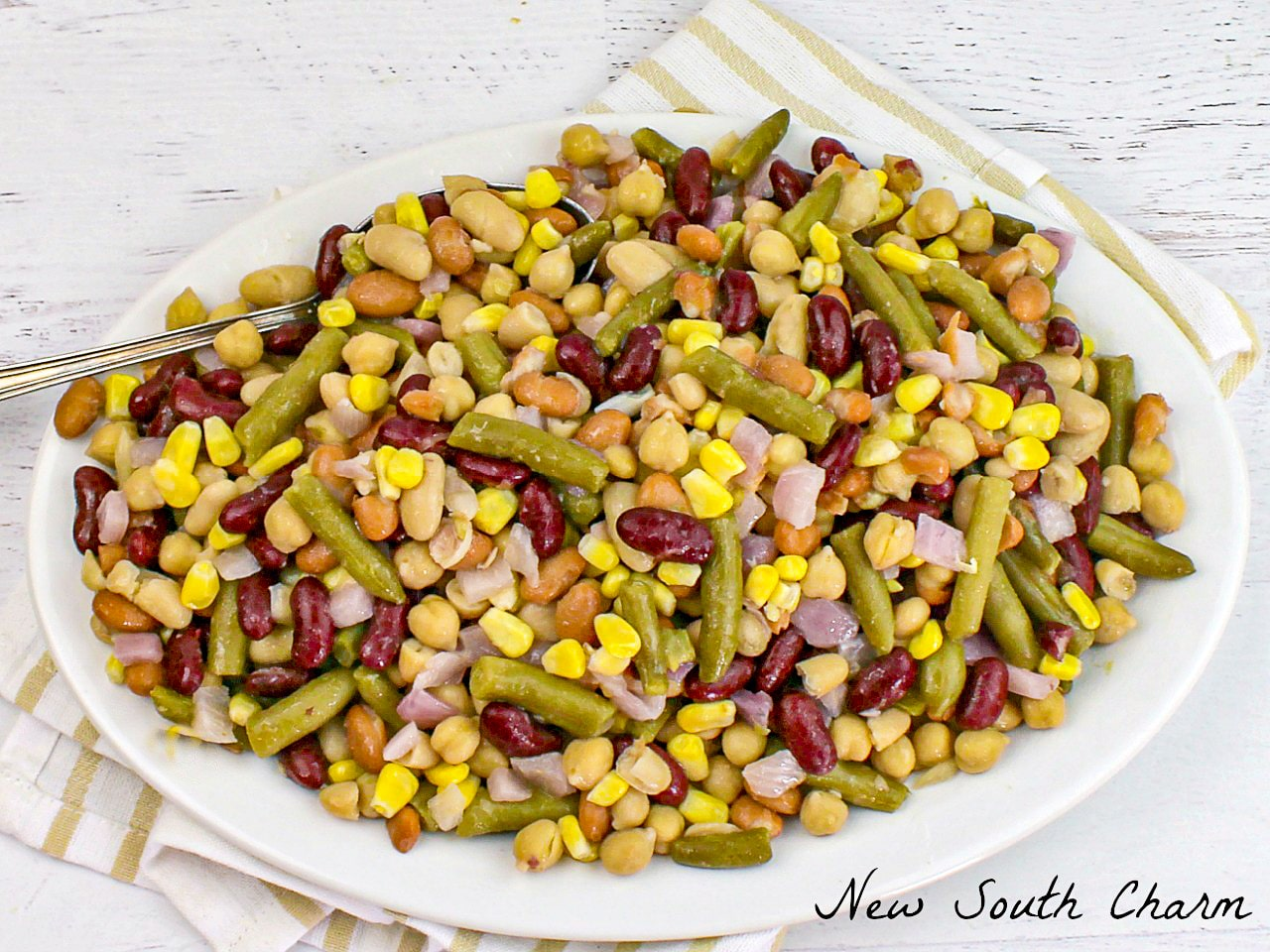 Five Bean Salad on a white platter with striped dish towel