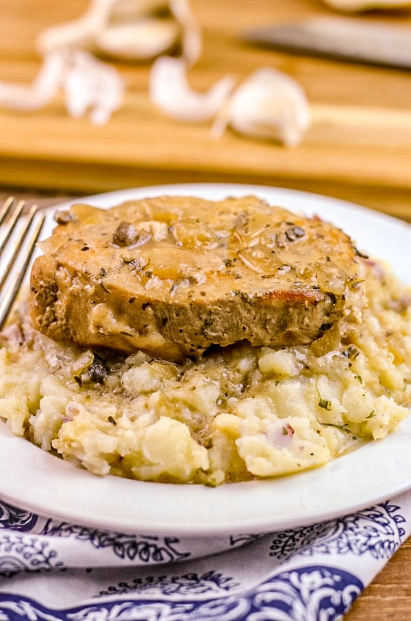 Slow Cooker Smothered Pork Chop on bed of mashed potatoes.