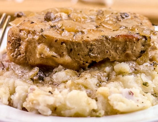 Crock Pot Smothered Pork Chops sitting on a bed of mashed potatoes with onion gravy.