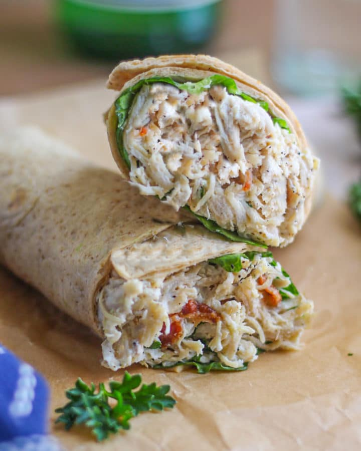 Caesar Chicken Wraps on brown parchment in front of a glass of sparkling water.