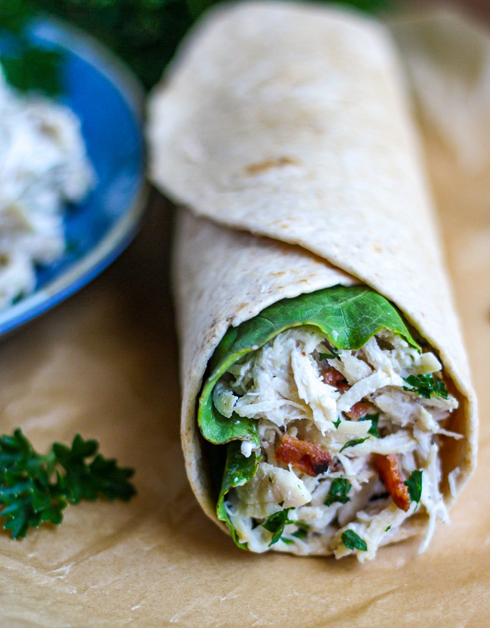 A single Caesar Chicken Wrap on brown parchment paper next to a blue bowl.