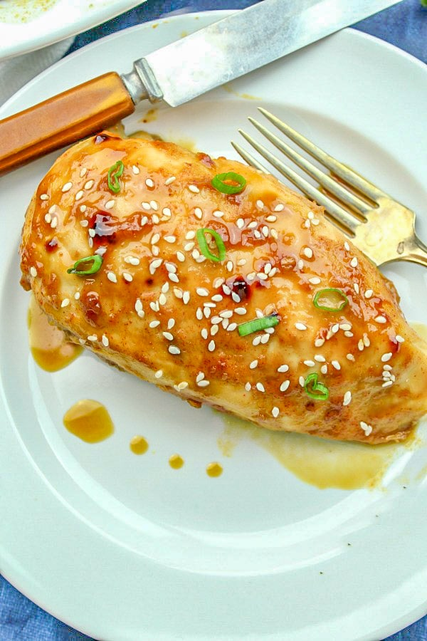 Single serving of Honey Garlic Chicken on a white plate with fork and knife.
