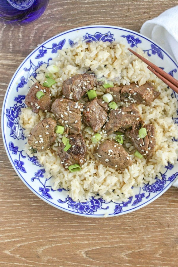 Teriyaki Steak Bites on top of rice with with sesame seeds and scallions on blue and white plate with chop sticks.