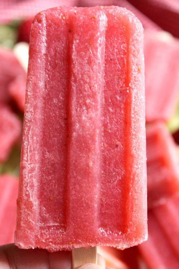 Woman's hand holding a Fresh Strawberry Daiquiri Popsicle on wooden stick