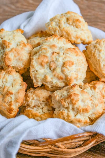 Easy Drop Biscuits in a straw basket lined with white towel on wooden cutting board