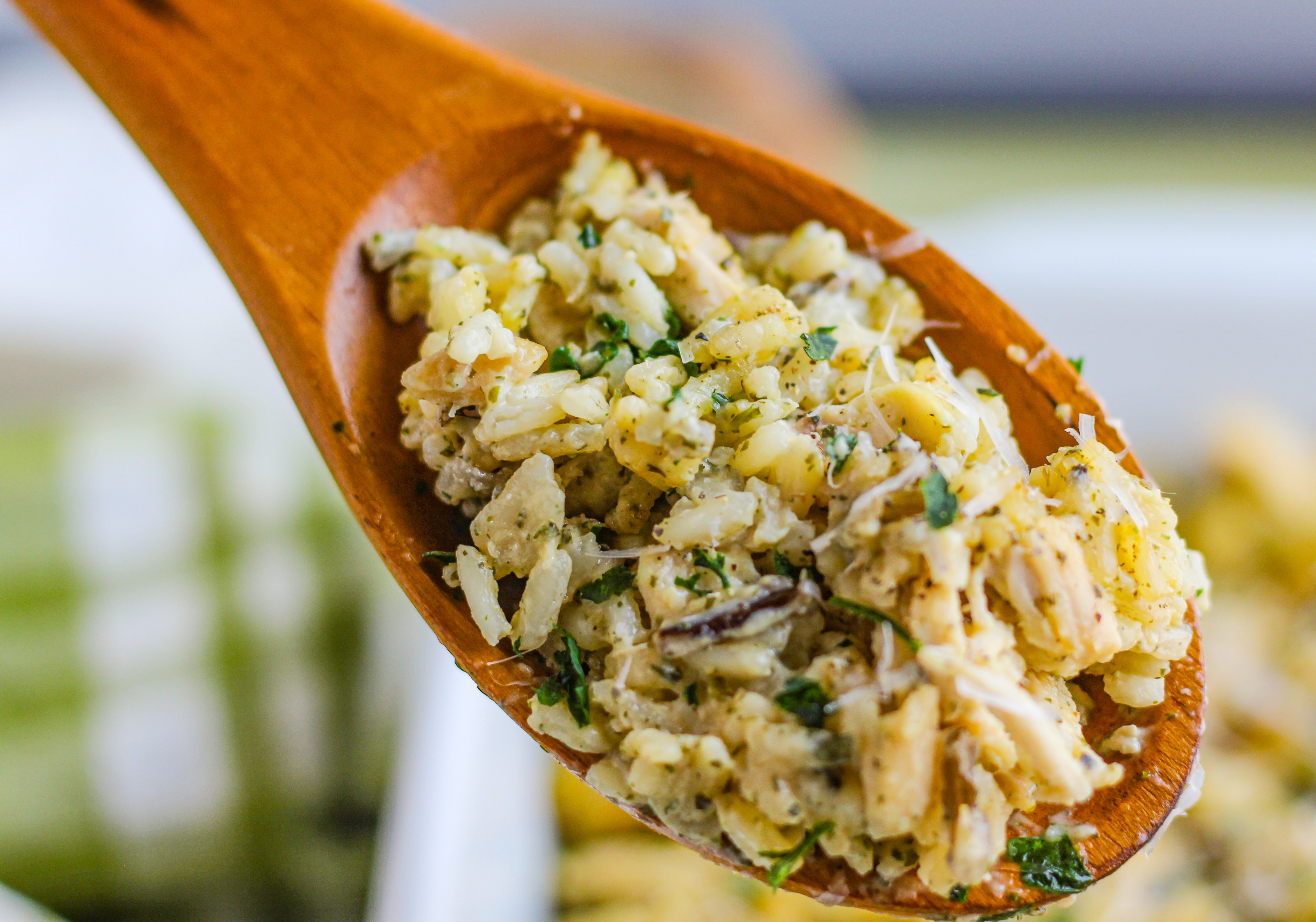 A wooden spoon with a scoop of chicken and rice.