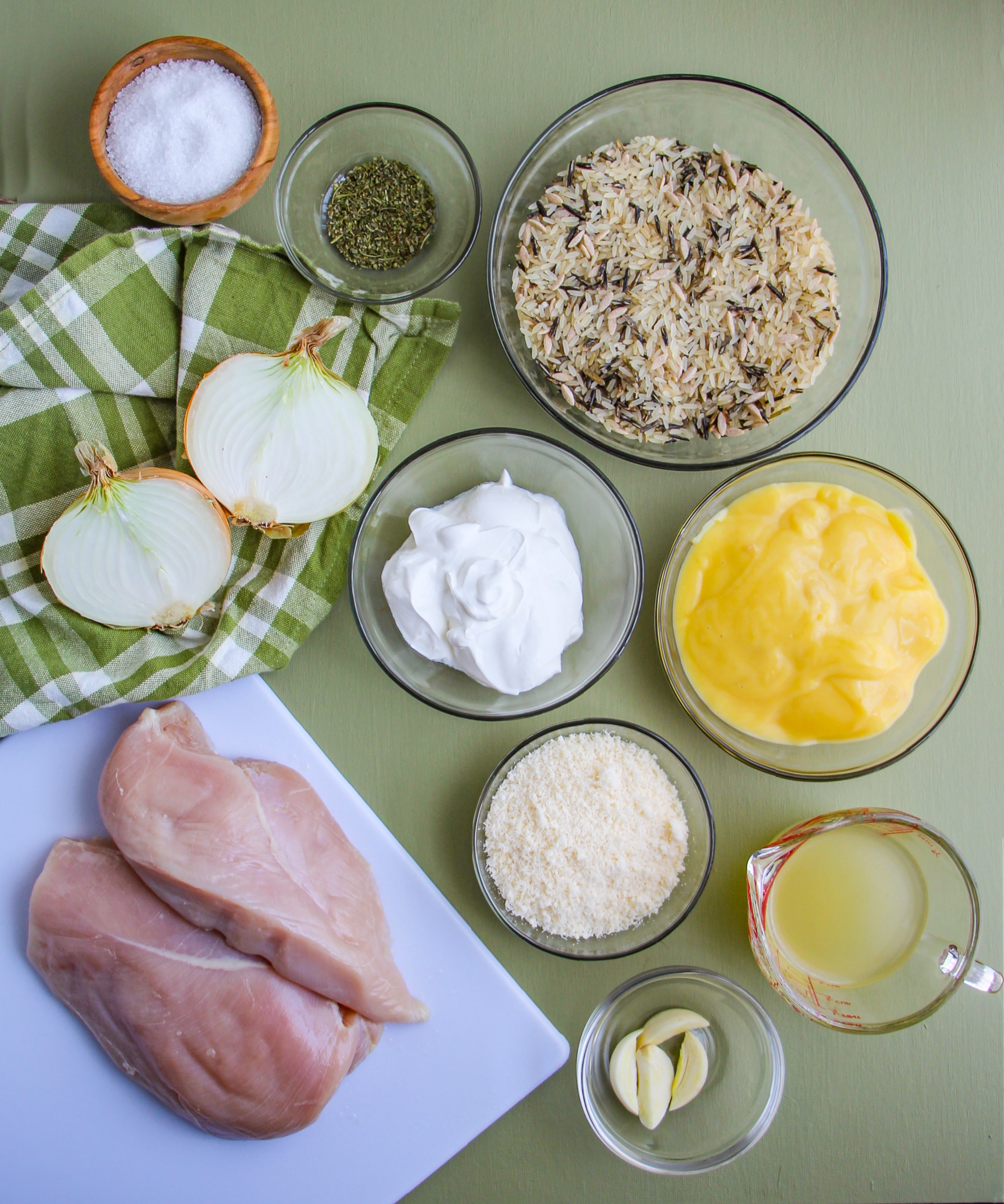 Ingredients need to make Chicken and Wild Rice Casserole displayed in clear glass bowls on a green background.
