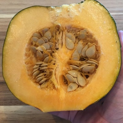 acorn squash sliced in half with seeds still in the middle
