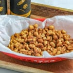 Slow Cooker Sweet and Spicy peanuts in a red plastic basket with white parchment with two bottles of beer on a wooden tray