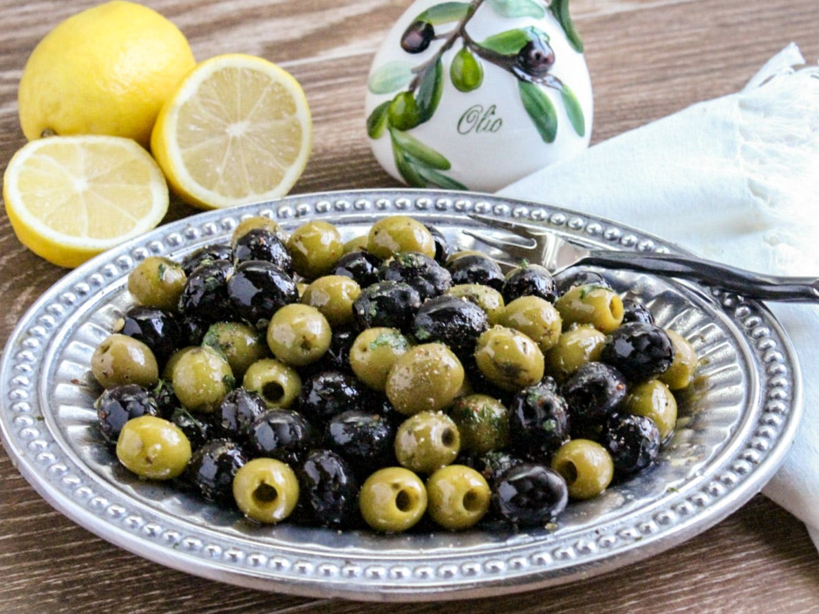 Mixture of green and black pitted olives on a pewter platter with sliced lemons and bottle of olive oil in background