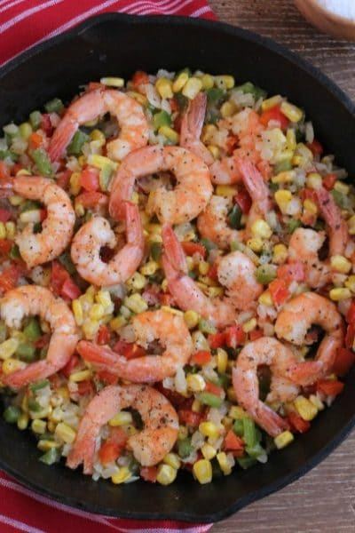 cajun seasoned shrimp with chopped onions and bell peppers and corn in a cast iron skillet on top of a red and white striped towel on wood background