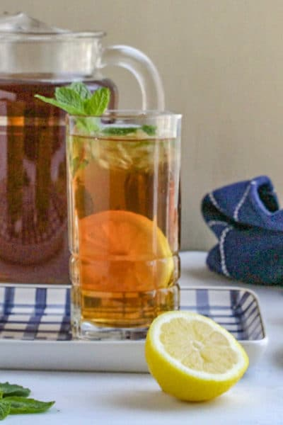 Glass of iced tea garnished with mint sitting on blue and white tray.
