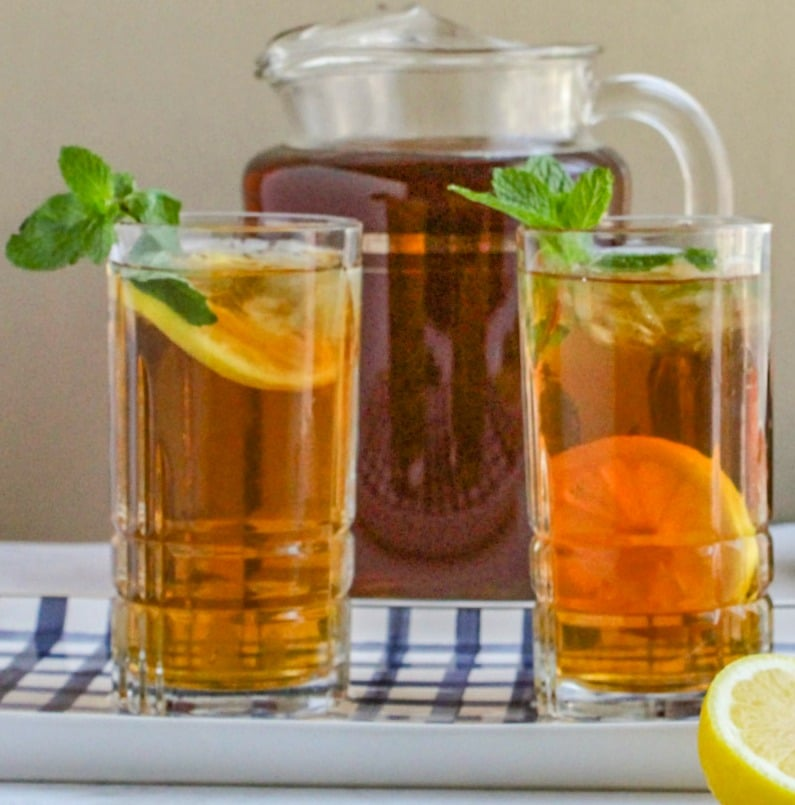 Two glasses of iced tea garnished with mint sitting on blue and white tray. with full pitcher of tea in background.