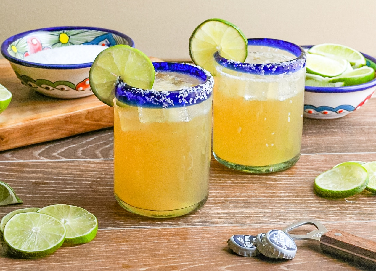 Two Beer Margaritas in a clear glass with salt lined rim and garnished with a slices of lime.