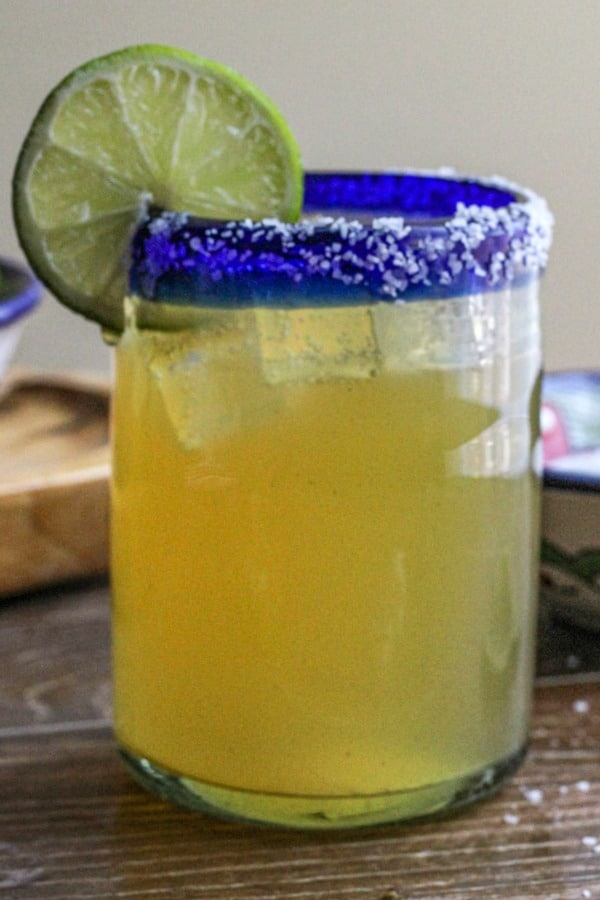 Beer margarita in a clear glass with salt lined rim and garnished with a slice of lime.