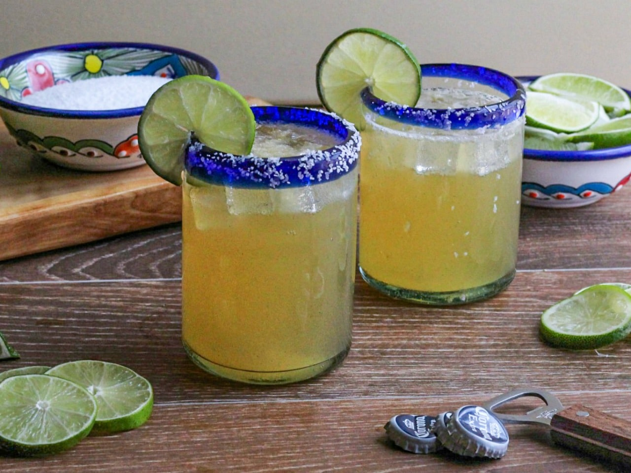 Two glasses or beer margarita on the rocks with salt lined rims and lime garnish.