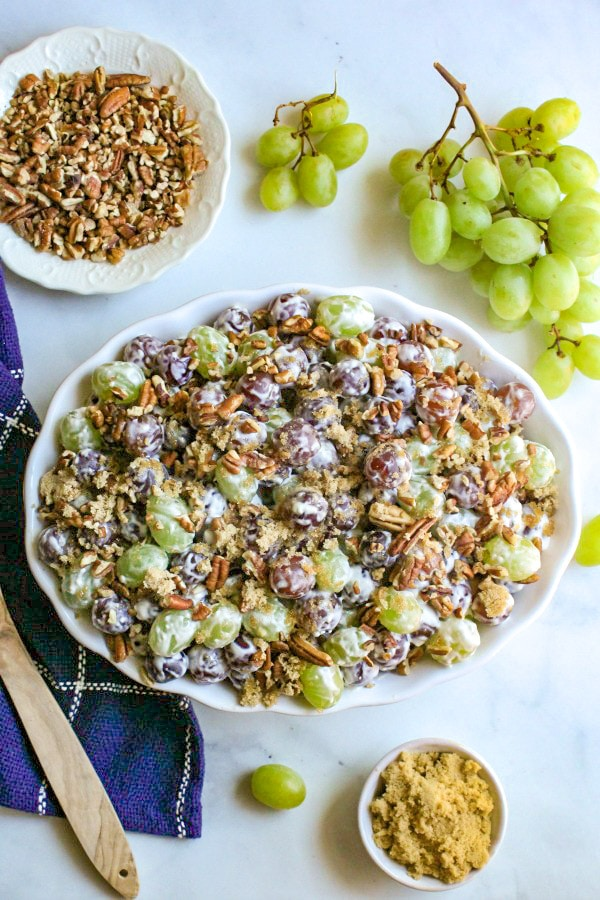 Grape salad in a white bowl topped with pecans and brown sugar next to a bunch of fresh green grapes and chopped pecans.