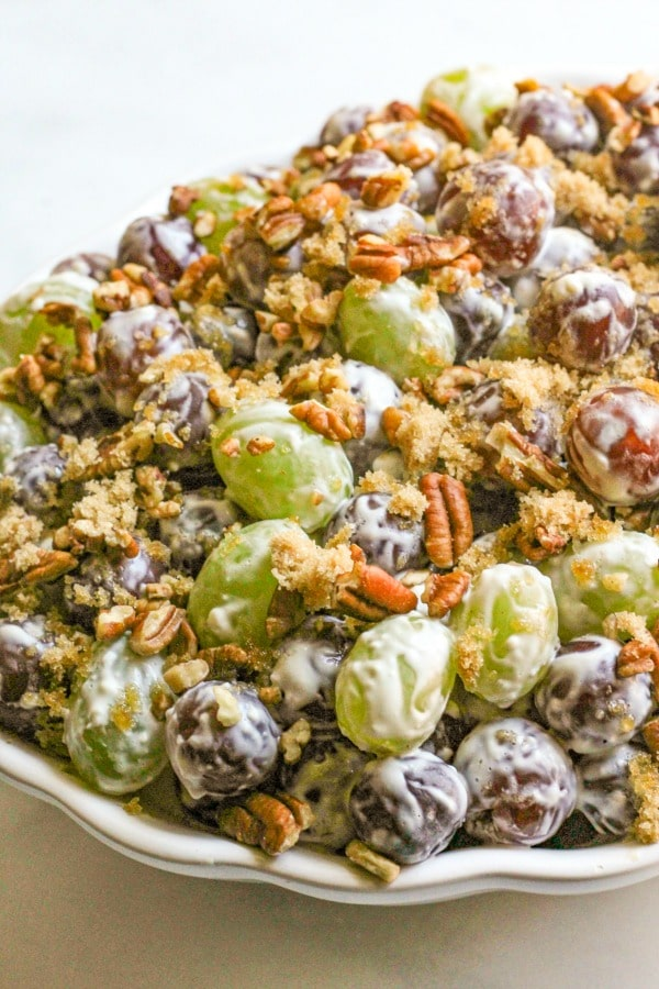 Close up of green and red grapes in cream cheese and brown sugar mixture with chopped pecans.