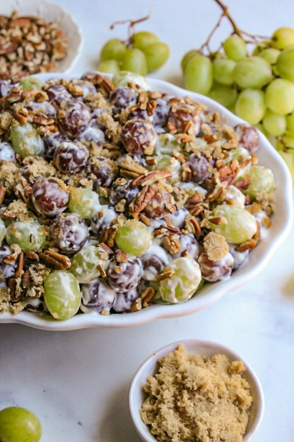 White serving bowl of Grape Salad garnished with brown sugar and pecans.