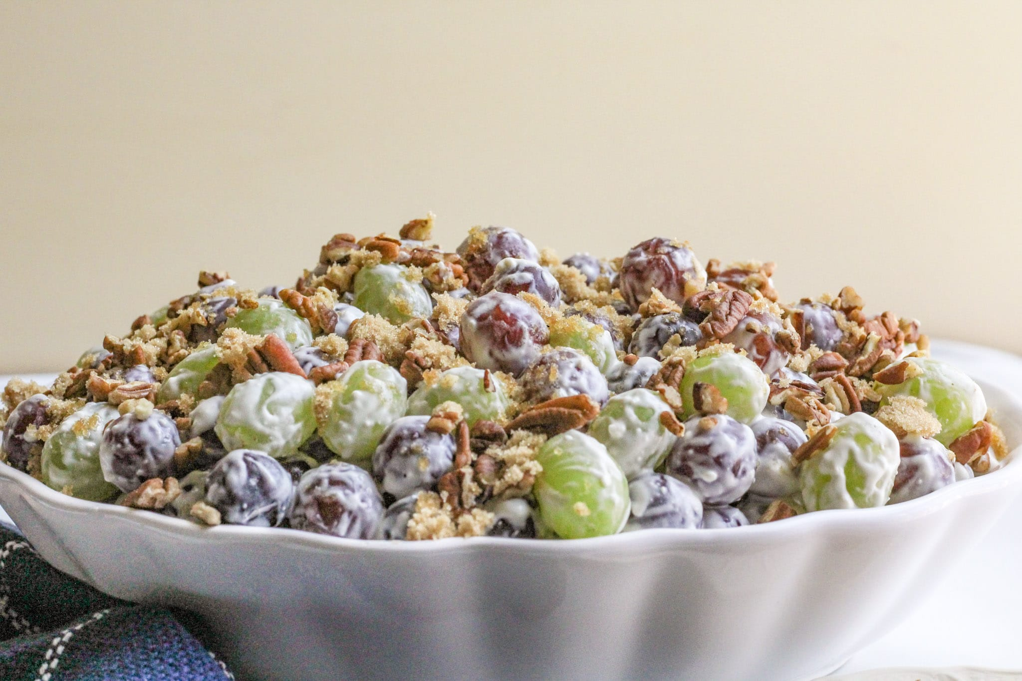 Grape Salad garnished with pecans and brown sugar piled high in a white serving bowl.