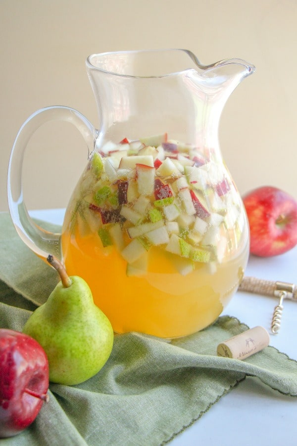 Clear glass pitcher with filled with Apple Pear Sangria garnised with chopped fruit.