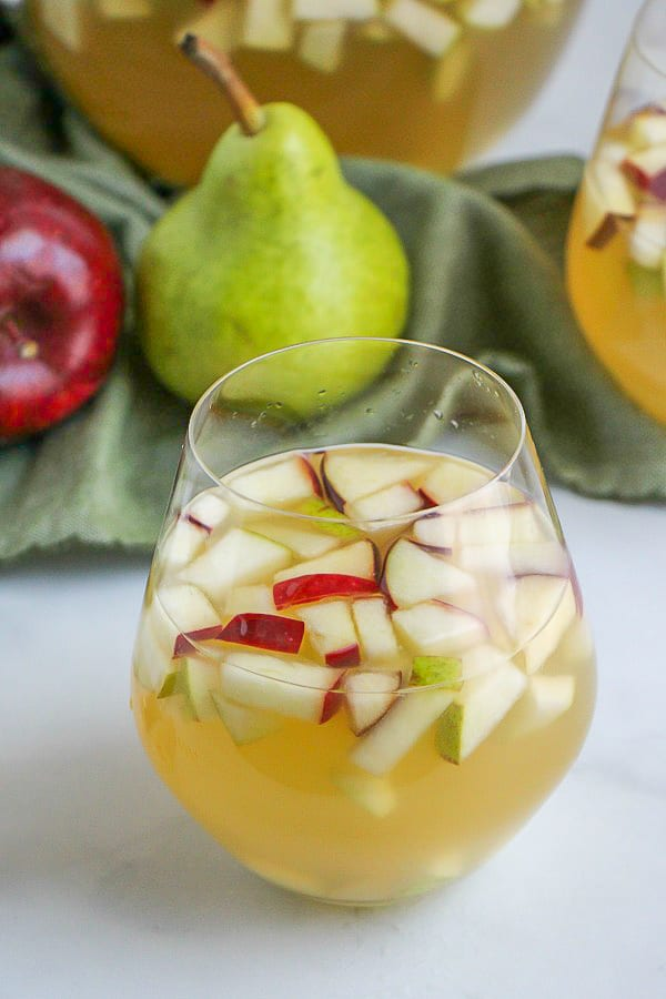 Stemless wine glass of sangria with chopped pieces of apple and pear.
