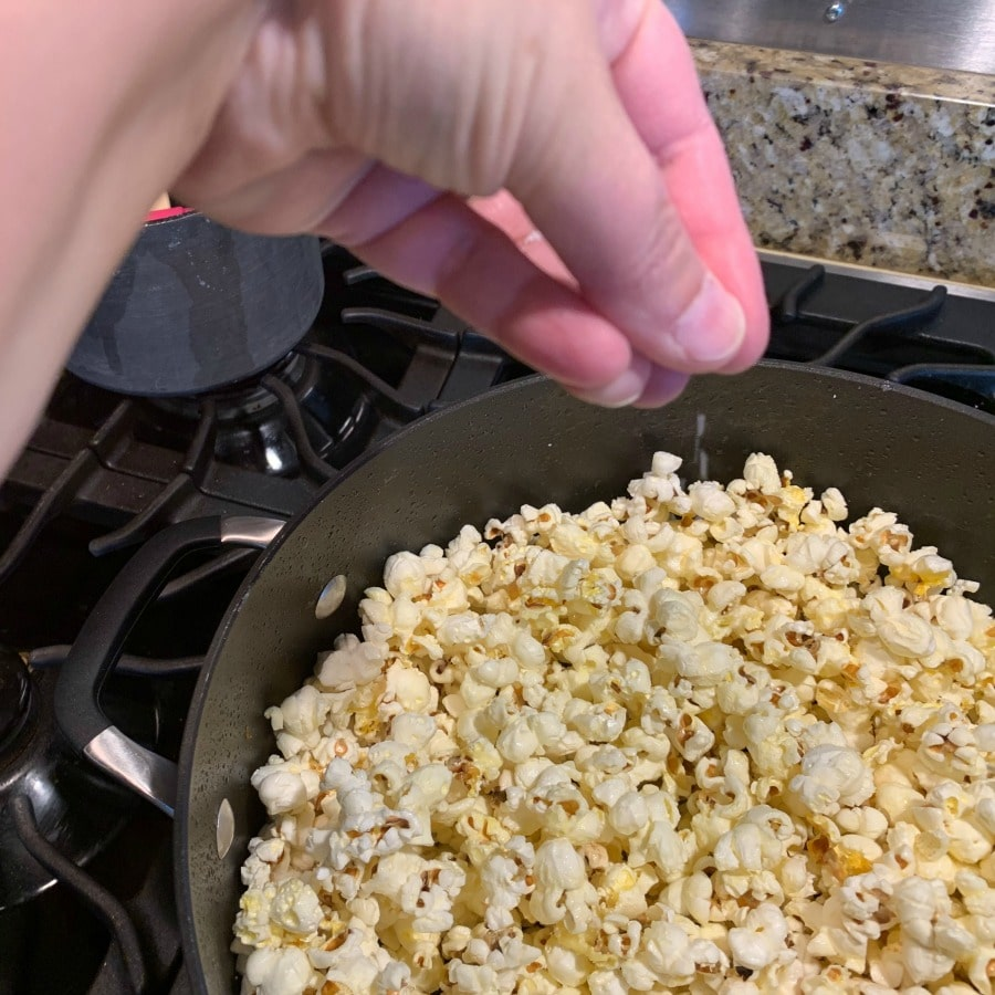 Photo of stovetop popcorn being salted.