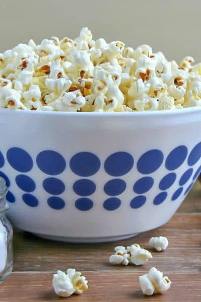 Stovetop Popcorn piled high is a white bowl with blue polka dots.