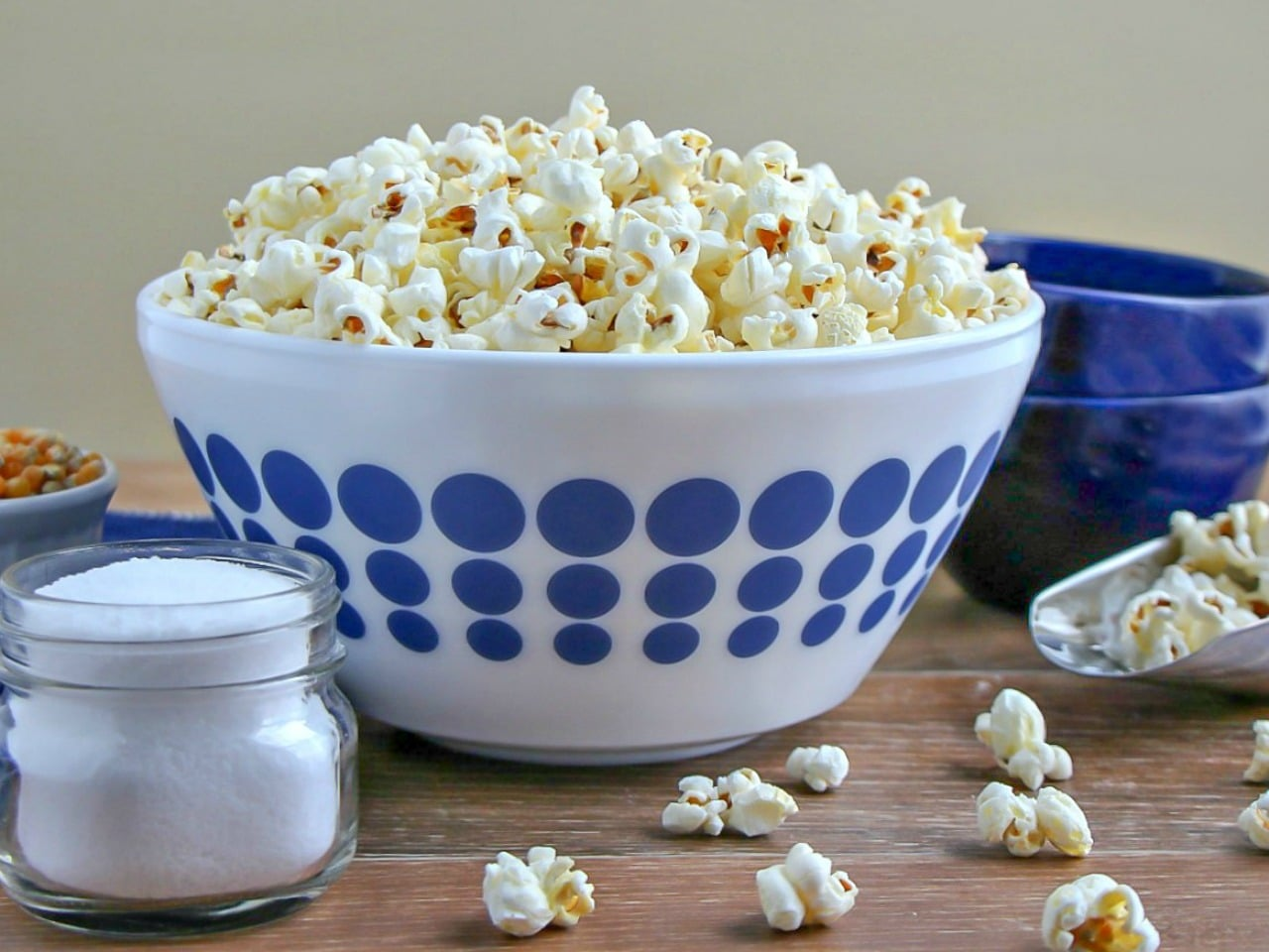 Stovetop Popcorn piled high in a white bowl with blue polka dots.