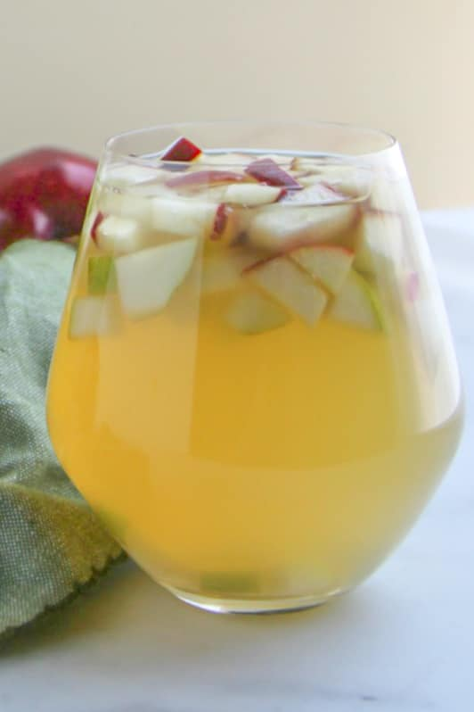 Close up picture of Pear and Apple Sangria in clear wine glass sitting next to a green napkin with a red apple in the background.