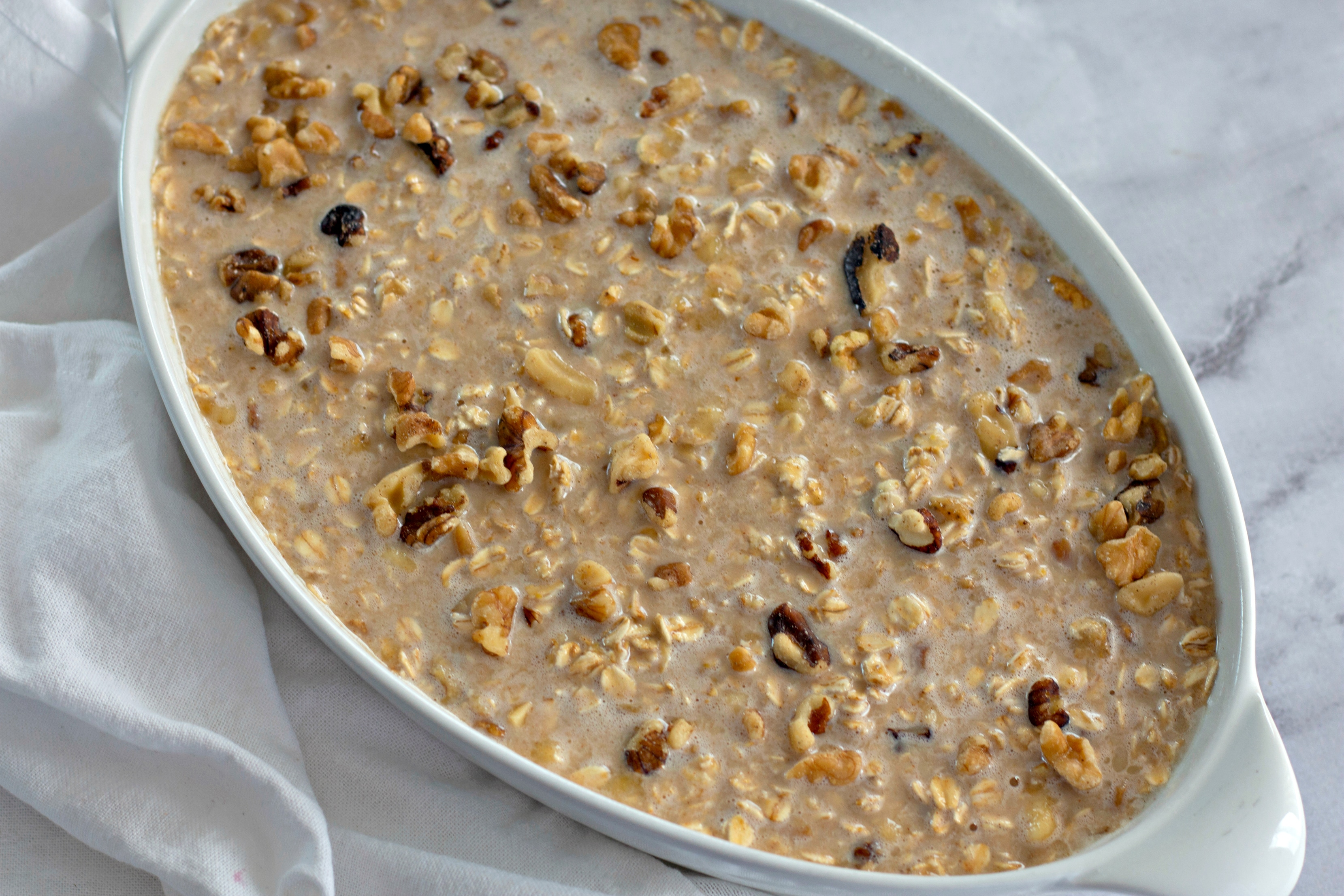 baked banana bread oatmeal prepped for the oven in white ceramic baking dish