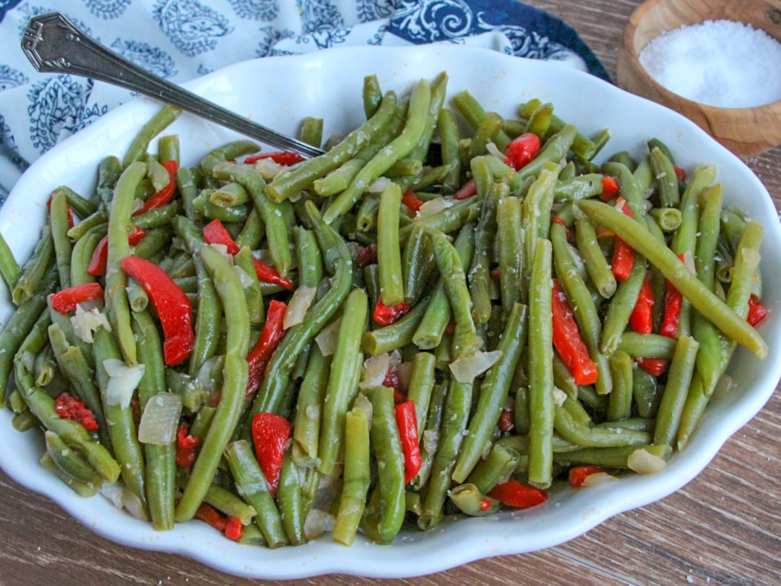 Green Beans with Roasted Red Peppers in white serving bowl with spoon
