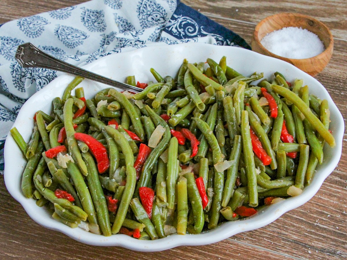 Green Beans with Roasted Red Pepper in a white serving bowl sitting on a blue and white napkin with a salt cellar.
