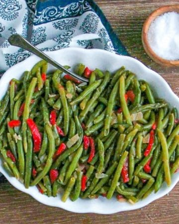 Green Beans with Roasted Red Peppers in a white serving bowl with vintage spoon and salt cellar.