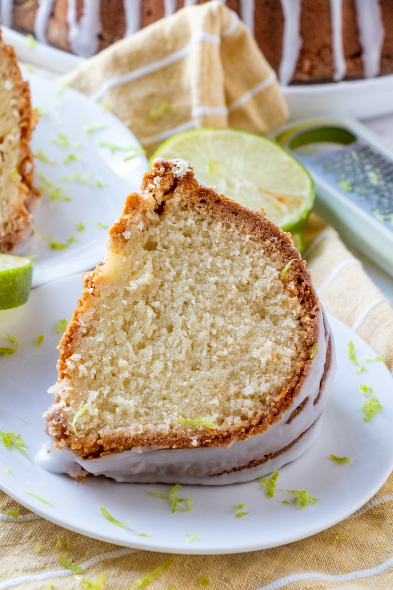 Slice of 7 Up Cake served on white plate with fresh lime zest garnish with lime slices on the side