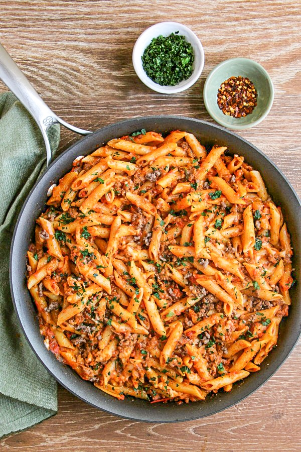 Mostaccioli Pasta in skillet with pinch bowls of parsley and red pepper flakes to the right.