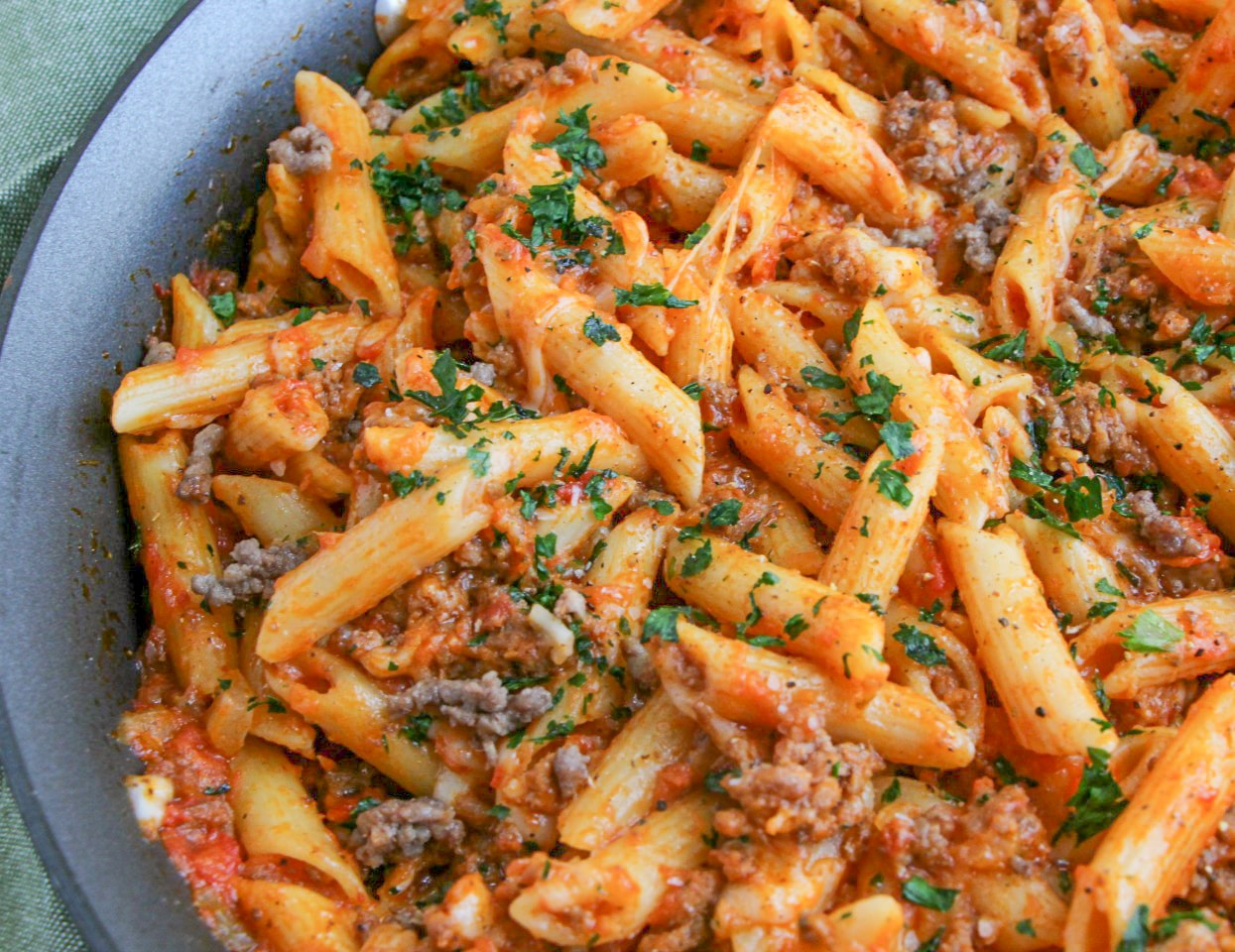Mostaccioli pasta prepared in a skillet with sausage and cheese and marinara sauce garnished with fresh parsley.