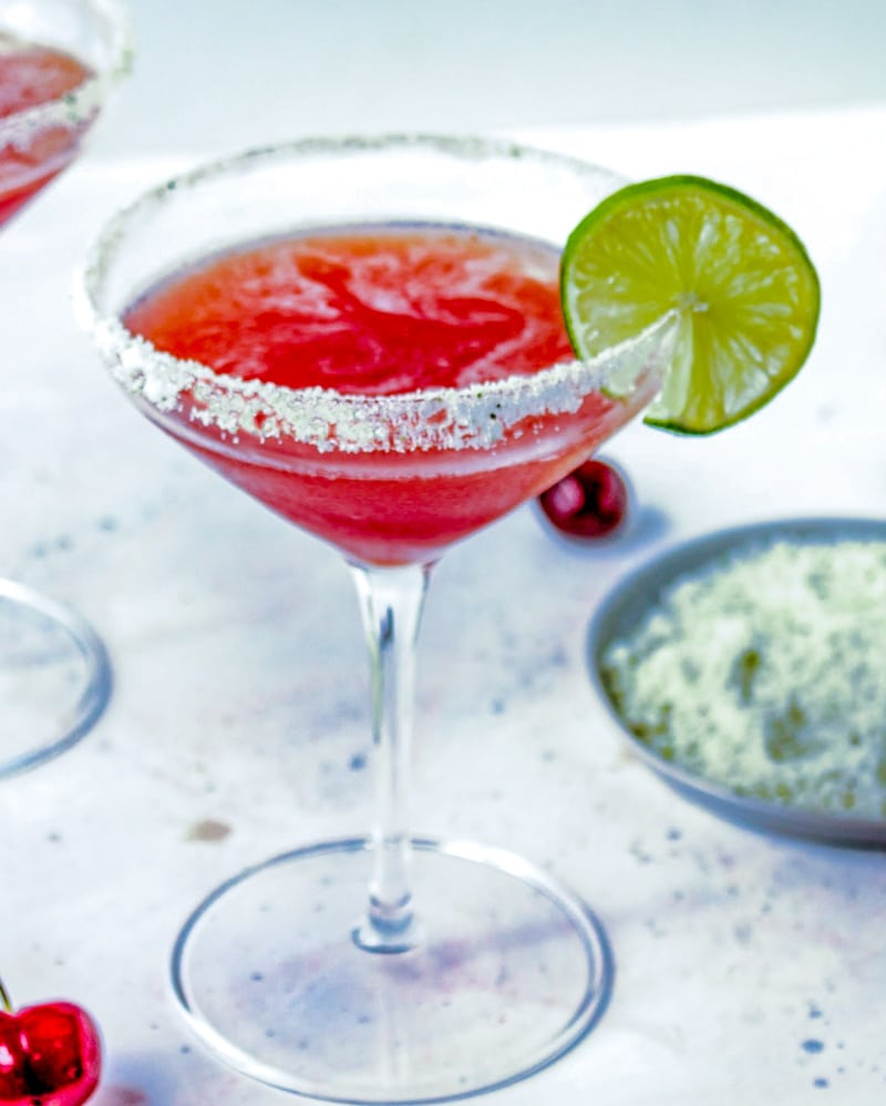A cocktail glass with salt rim and Cherry Lime Margaritas garnished with lime slices