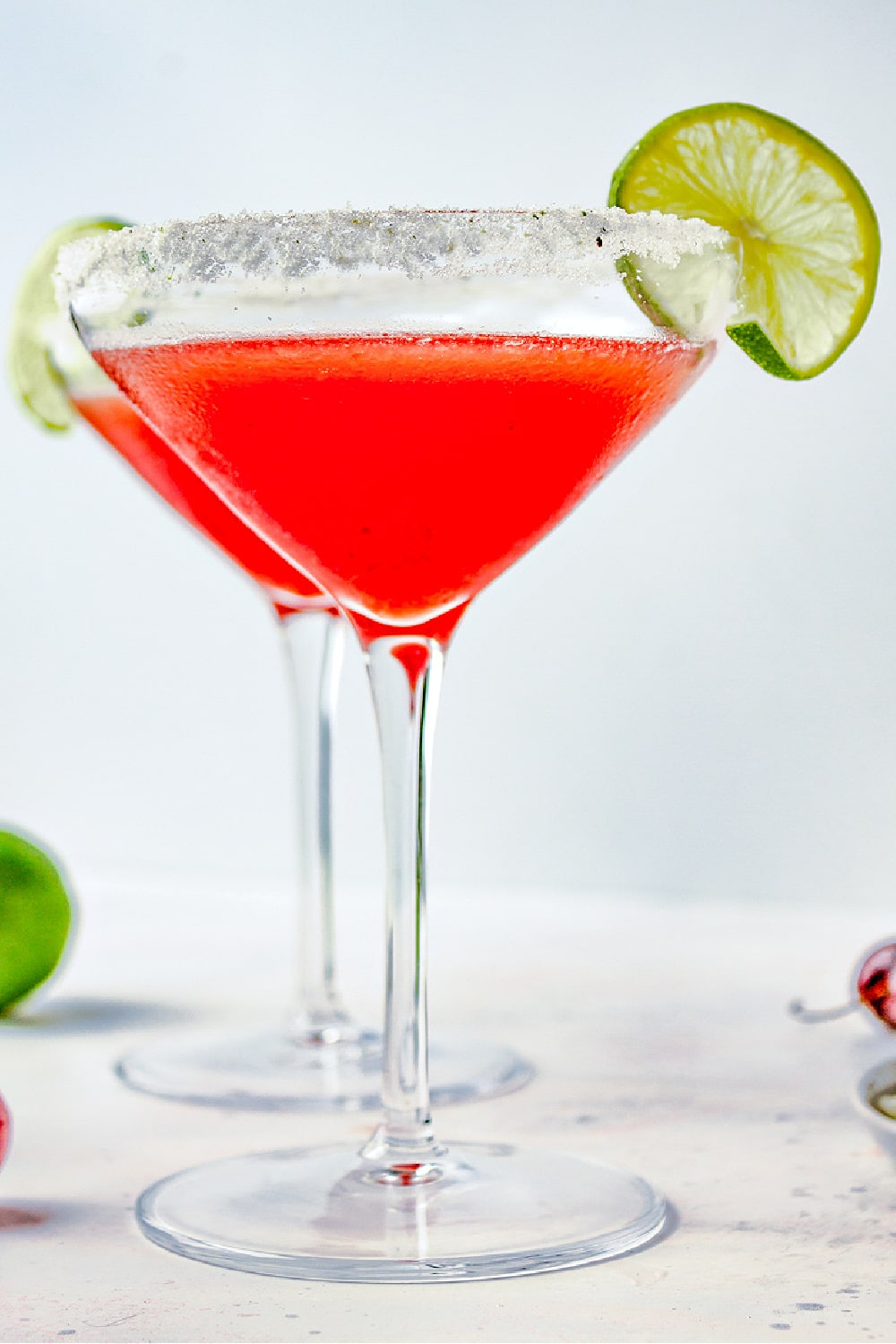 Two cocktail glasses with salt rims and Cherry Lime Margaritas garnished with lime slices