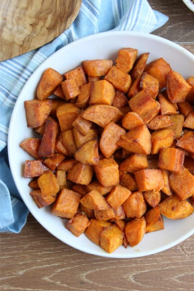 Cinnamon and Brown Sugar Sweet Potatoes in a white bowl on wooden cutting board with blue dish towel and spoon