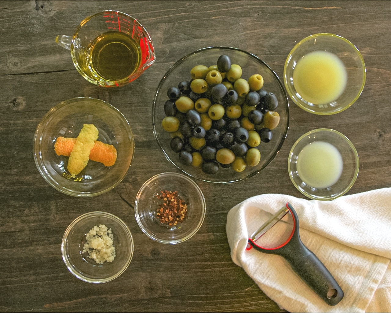 Ingredients needed to make Citrus Marinaded Olives on a wood cutting board.