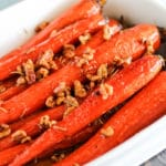 Honey and Maple Glazed Carrots in a garnished with walnuts and rosemary in white serving dish