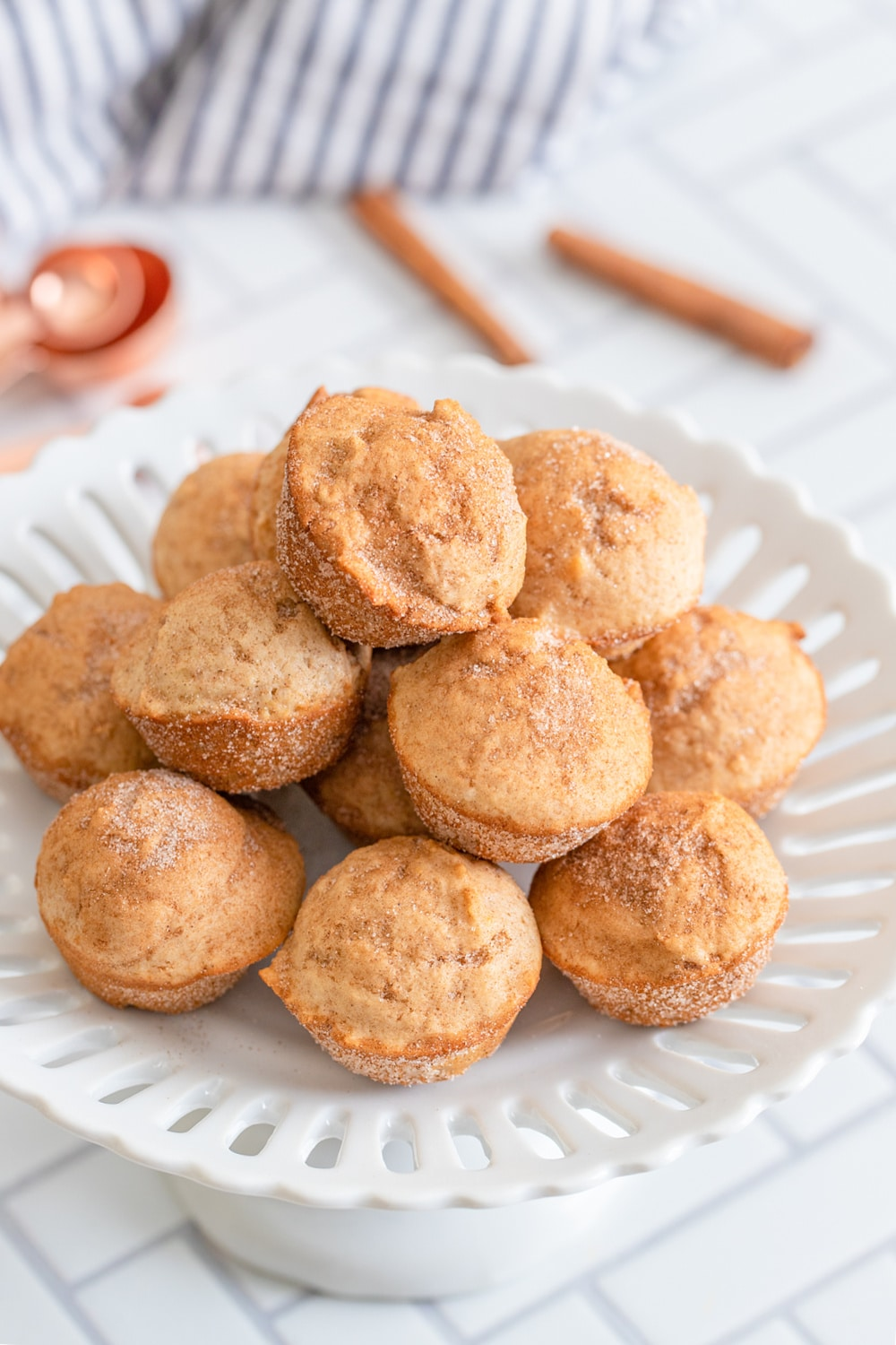 A dozen Cinnamon Sugar Mini Muffins on a white dish