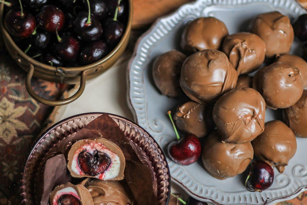 Cherry Cordials on a grey plate next to a sliced cordial in a pink bowl
